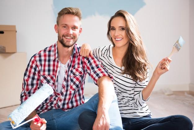 Retrato de casal pintando seu novo apartamento