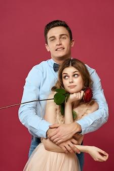 Retrato de casal romântico apaixonado por uma rosa vermelha em espaço isolado e vestido de noite de terno clássico.