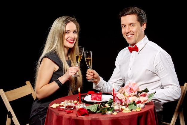 Retrato de casal romântico brindando vinho branco no jantar