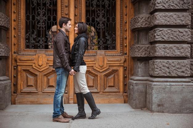 Retrato de casal romântico em pé ao ar livre com a velha porta de madeira no bacground
