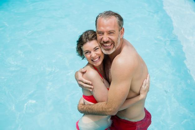 Retrato de casal romântico se abraçando na piscina sorridente