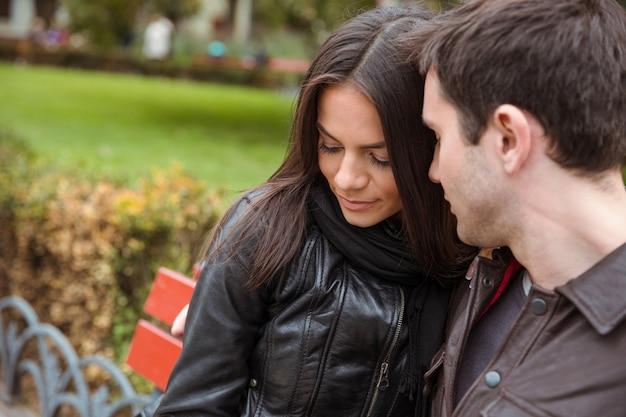 Retrato de casal romântico sentado no banco ao ar livre