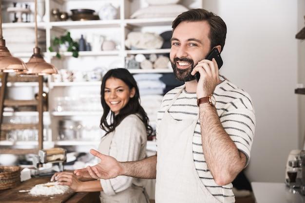 Retrato de casal satisfeito, homem e mulher de 30 anos, usando aventais, usando smartphone, enquanto cozinham juntos na cozinha de casa
