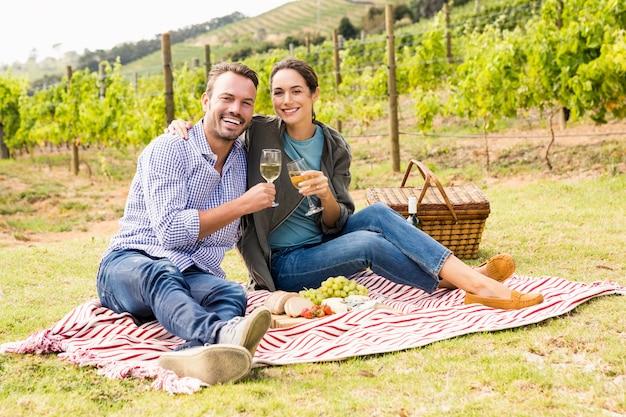 Retrato de casal segurando um copo de vinho na vinha