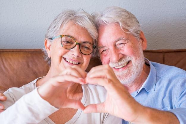 Retrato de casal sênior alegre, abraçando-se ao fazer o gesto de forma de coração com as mãos. casal feliz de idosos relaxando e posando na frente da câmera, sentado na sala de estar.