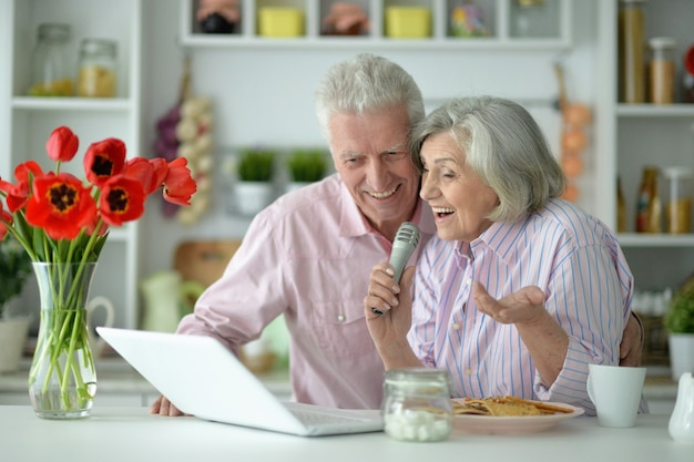 Retrato de casal sênior com microfone e laptop