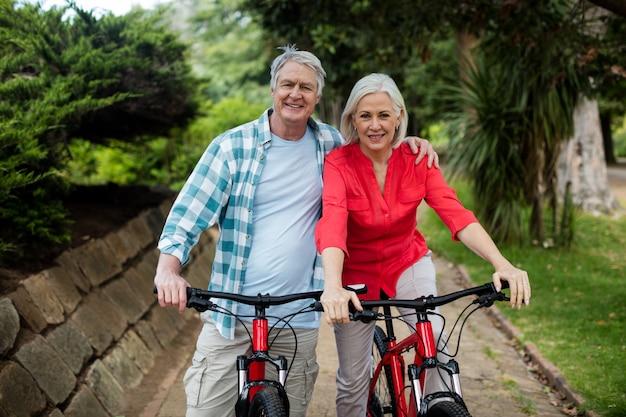 Retrato de casal sênior dançando com bicicleta no parque