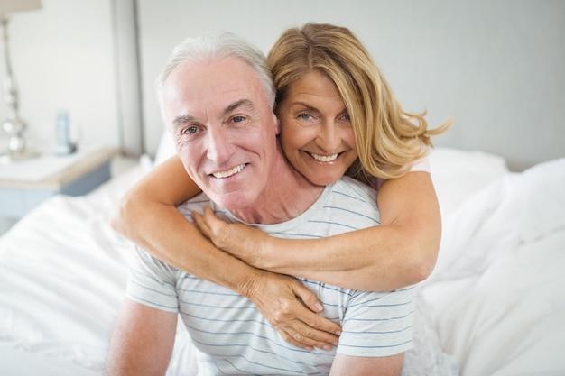 Retrato de casal sênior feliz, abraçando-se na cama Foto Premium