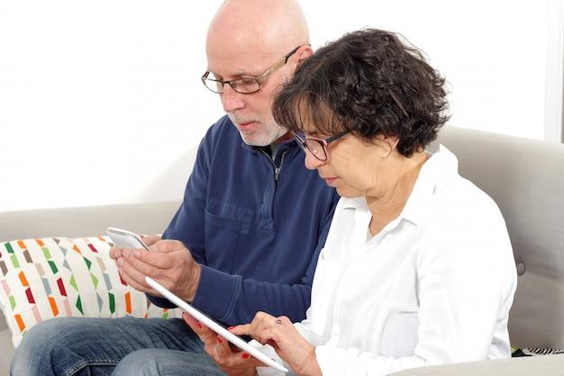 Retrato de casal sênior feliz usando tablet e telefone