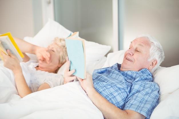 Retrato de casal sênior lendo na cama