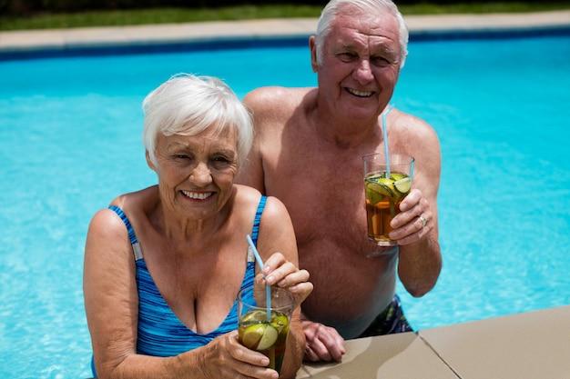Retrato de casal sênior segurando copos de chá gelado na piscina