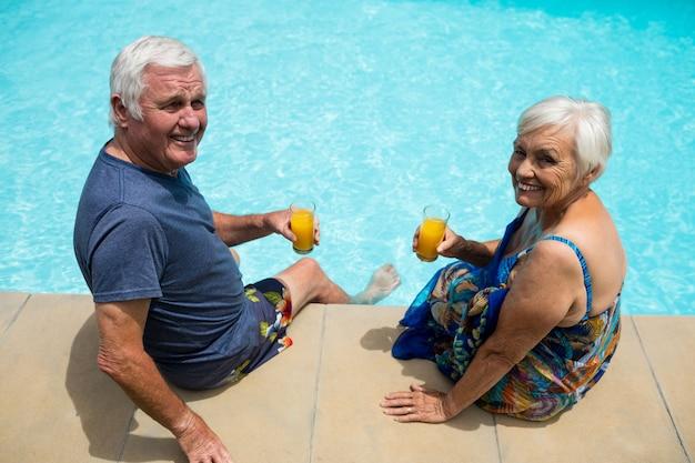 Retrato de casal sênior segurando copos de suco perto da piscina