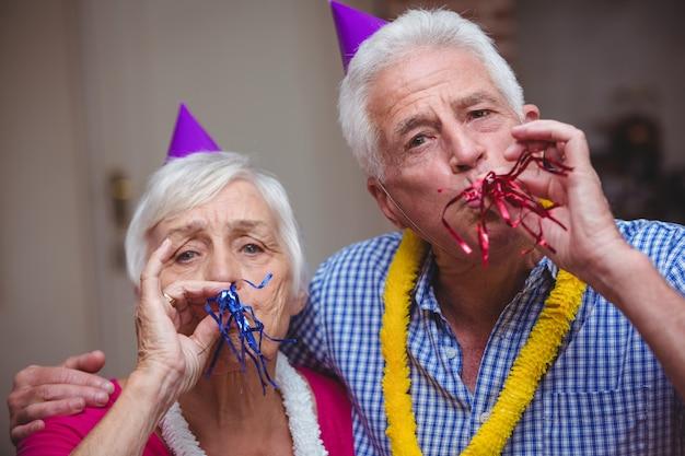 Retrato de casal sênior soprando corneta de festa
