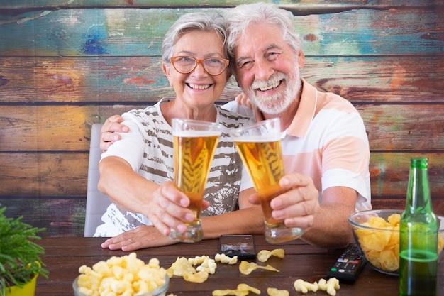 Retrato de casal sênior sorridente brindando com cervejas, sentado à mesa de madeira, olhando para a câmera