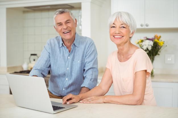 Retrato de casal sênior usando laptop na cozinha
