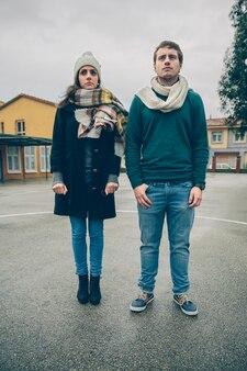 Retrato de casal sério, vestindo roupas de inverno, em pé ao ar livre em um dia frio e chuvoso