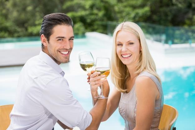 Retrato de casal sorridente bebendo vinho