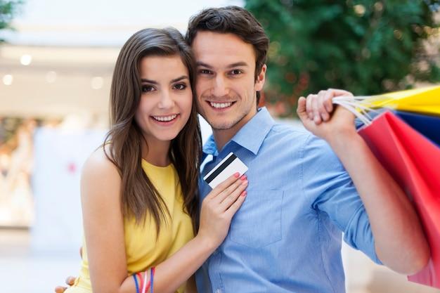 Retrato de casal sorridente com cartão de crédito e sacolas de compras
