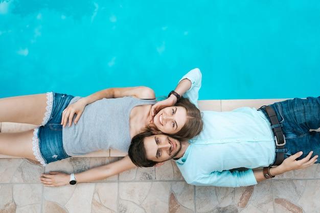Retrato de casal sorridente deitado vestido perto da piscina. eles se adoram