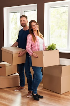 Retrato de casal sorridente durante a mudança para casa