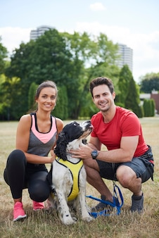 Retrato de casal sorridente e seu cachorro após o treino