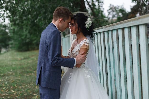 Retrato de casal sorridente feliz noivas ao ar livre. apenas casal em uma caminhada no parque verde primavera. recém-casados emocionais beijam e abraçam durante uma caminhada no casamento. dia do casamento.