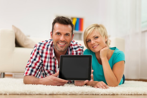 Retrato de casal sorridente mostrando a tela do tablet digital em casa