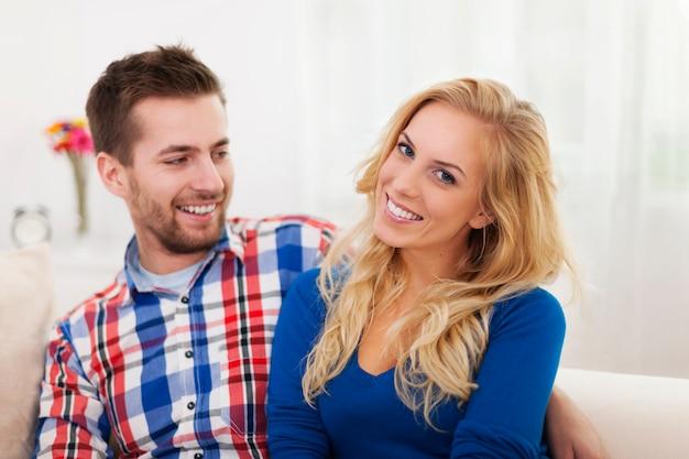 Retrato de casal sorridente na sala de estar