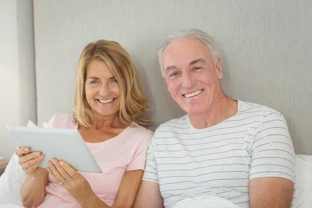 Retrato de casal sorridente usando tablet digital na cama