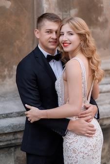 Retrato de casal sorriu no vestido elegante e smoking preto perto da parede de pedra
