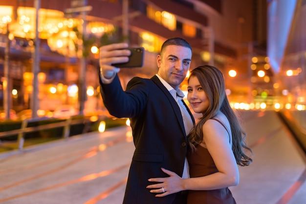 Retrato de casal tirando selfie com telefone ao ar livre à noite na cidade de bangkok, tailândia