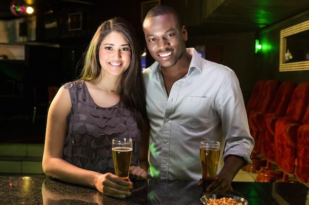 Retrato de casal tomando cerveja no balcão de bar em bar