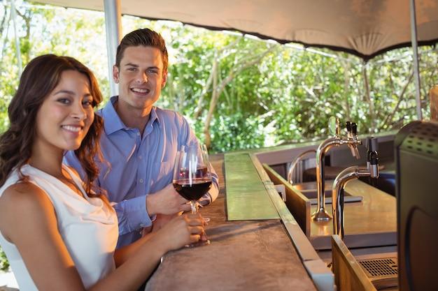 Retrato de casal tomando uma taça de vinho tinto no balcão