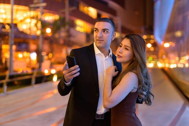 Retrato de casal usando telefone ao ar livre à noite na cidade de bangkok, tailândia