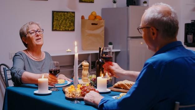 Retrato de casal velho sênior feliz brindando vinho em casa durante um jantar romântico. idosos maduros, sentados à mesa da cozinha, apreciando a refeição, comemorando aniversário na sala de jantar.