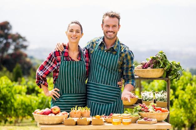 Retrato de casal vendendo legumes
