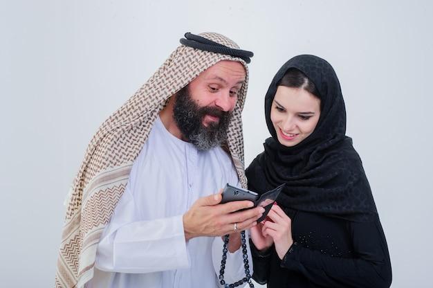 Retrato de casal vestido de maneira árabe brincar com o telefone celular.
