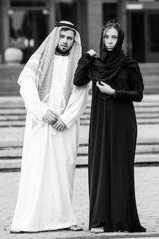 Retrato de casal yang vestido de árabe brincar com o telefone celular.