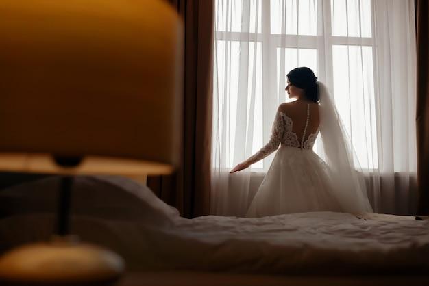 Retrato de casamento da noiva na frente de uma janela. retrato da beleza da noiva usando vestido de casamento da moda.