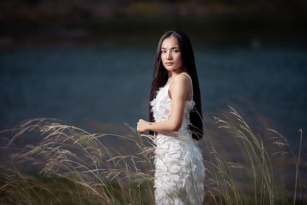 Retrato de casamento de uma noiva fofa mulher asiática vestido de noiva branco lindo do designer na rocha e na floresta, estilo vintage