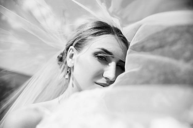 Retrato de casamento de uma noiva sob um véu branco. uma garota com um vestido de noiva segurando um buquê de flores nas mãos
