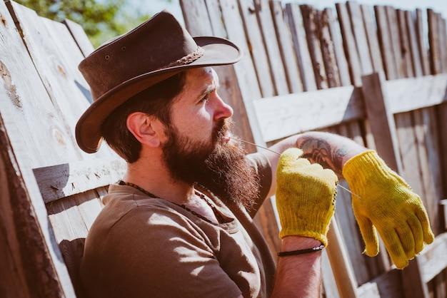 Retrato de caubói ocidental jardineiro barbudo em um hobby de jardinagem em um jardim urbano com cena rural