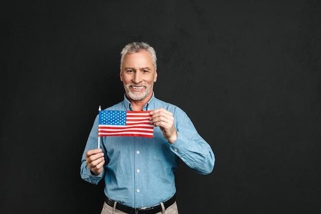 Retrato de caucasiano pensionista masculino dos anos 60 com cabelos grisalhos e barba na camisa segurando a pequena bandeira americana com orgulho e sorrindo, isolado sobre a parede preta
