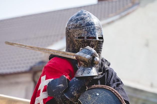 Retrato de cavaleiro com capacete e espada na mão