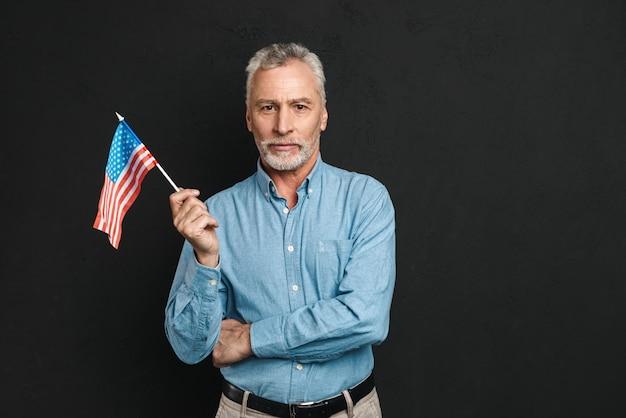Retrato de cavalheiro profissional dos anos 50, com cabelos grisalhos e barba na camisa segurando seriamente a pequena bandeira americana, isolada sobre parede preta