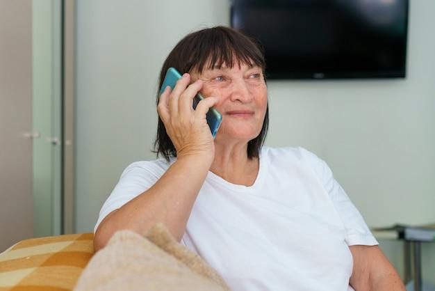 Retrato de celular da alegre avó caucasiana ligando com a família enquanto está sentado no sofá no mod.
