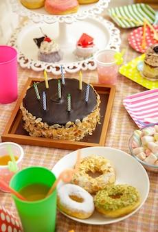 Retrato de cheesecake de chocolate, donuts, minibolo e marshmallow na mesa posta para festa infantil