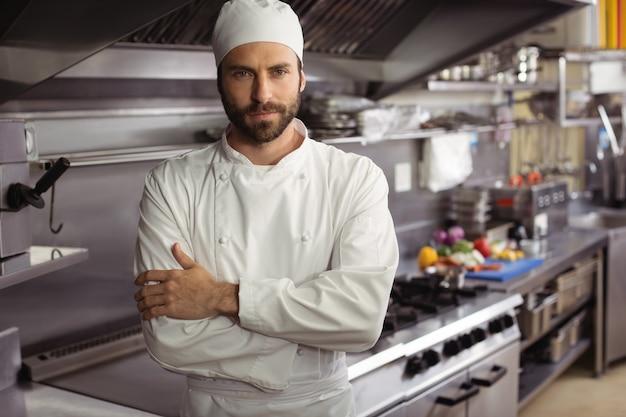 Retrato de chef confiante em pé com os braços cruzados em uma cozinha comercial