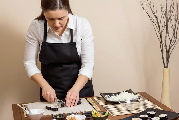 Retrato de chef mulher cortando rolos de sushi japonês com arroz, abacate e camarão em folha de alga nori