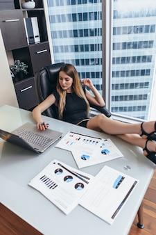 Retrato de chefe feminino relaxado, sentado no local de trabalho com os pés na mesa, planejando seus objetivos de escrita do dia de trabalho no caderno.